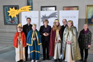 """Die Sternsinger (v.l.n.r.) Fabian Lamm (12), Julius Petersilka (10), Tina Noppenberger (13) und Anna-Lena Dittrich (12) sowie Begleiterin Dagmar Haas  (re. au�en) aus der Gemeinde St. Stephanus in Adelsdorf vertraten das Erzbistum Bamberg am Dienstagmorgen beim Sternsinger-Empfang von Bundeskanzlerin Angela Merkel zur 58. Aktion Dreik�nigssingen. Zum Gruppenfoto mit der Kanzlerin stellten sie sich gemeinsam mit Pr�lat Dr. Klaus Kr�mer (li.), Pr�sident des Kindermissionswerks """"Die Sternsinger"""", und Pfr. Dirk Bingener (re.), Bundespr�ses des Bundes der Deutschen Katholischen Jugend (BDKJ), im Bundeskanzleramt auf. Foto: Ralf Adloff"""