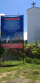 Plakat und Glockenturm am Eingang des Schönstattzentrums